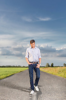 Full length of young man walking on empty rural road