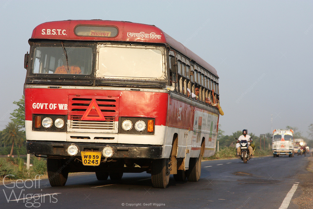 Indian Ashok Leyland bus of the South Bengal State Transport Corporation (SBSTC) travels up highway at sunset, West Bengal, India