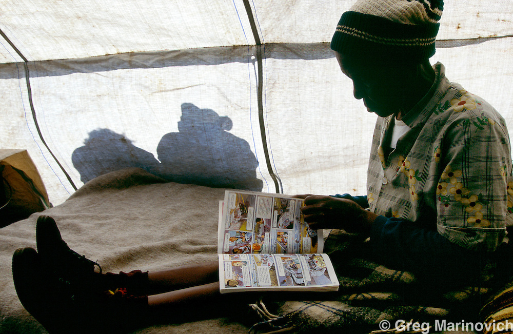 Sonkombo, KwaZulu Natal, 1994, South Africa: An ANC supporting woman passes time in a refugee camp after ANC supporting families  fled months earlier because of attacks by rival IFP in the Sonkombo area.