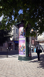 An advertising kiosk adds color to an intersection of the old Roman city of Orange in the Vaucluse department of Provence in southern France.