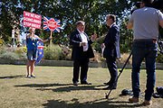 A day after British Prime Minister Boris Johnson successfully asked the Queen to suspend (prorogue) Parliament in order to manoeuvre his Brexit deal with the EU in Brussels, a Remain protester holds up placards during a TV interview between Channel4 News' Gary Gobbon and ERG member Mark Francois on College Green, on 29th August 2019, in Westminster, London, England.