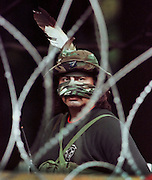 A Mohawk Warrior stands behind barbed wire during a standoff with the Canadian military in Oka, Que. (1990)