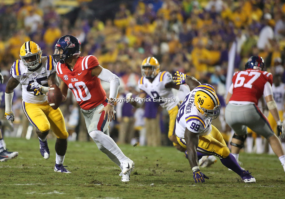 Sep 29, 2018; Baton Rouge, LA, USA; LSU Tigers linebacker Michael Divinity Jr. (45) and defensive tackle Ed Alexander (99) pursue Mississippi Rebels quarterback Jordan Ta'amu (10) during the second quarter of a game at Tiger Stadium. Mandatory Credit: Derick E. Hingle-USA TODAY Sports