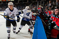 KELOWNA, BC - NOVEMBER 6: Will Warm #4 of the Victoria Royals checks Leif Mattson #28 of the Kelowna Rockets into the boards in front of the home bench during first period at Prospera Place on November 6, 2019 in Kelowna, Canada. (Photo by Marissa Baecker/Shoot the Breeze)