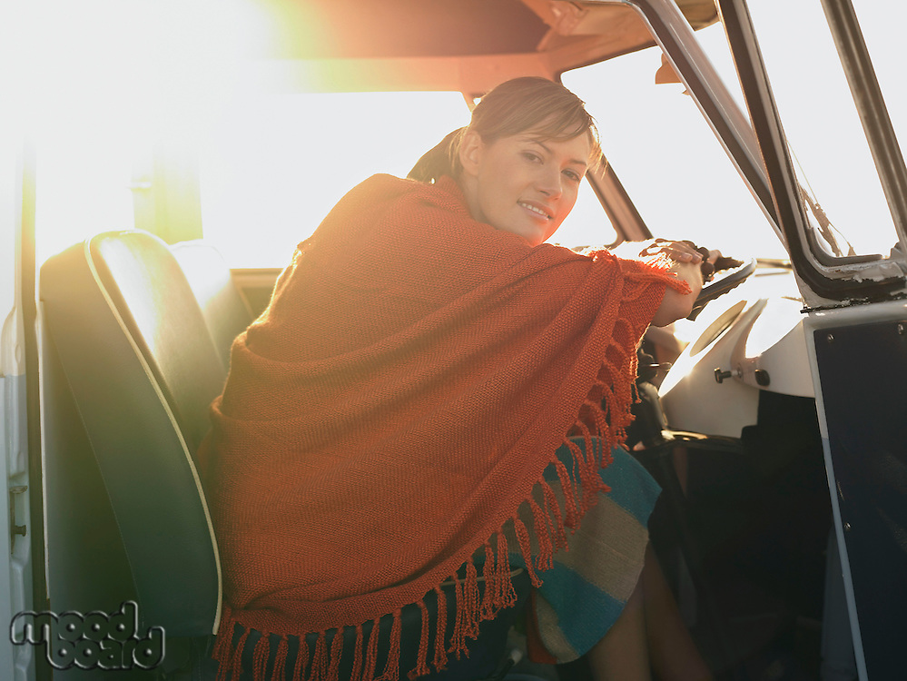 Woman in poncho sitting in front seat of van