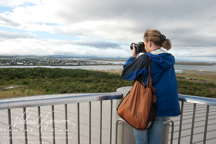 Tanya Cox photographing city of Reykjavik from observation deck of Saga Museum. Iceland.