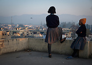 Fifty young girls have been given the opportunity to live, learn and become independent women at the 66 year old Akhil Bharatiya Mahila Ashram in Dehradun, Uttarakhand, India. Here, an older girl has invited her younger friend to the rooftop of the ashram where she looks out over the town and Himalaya mountains in a contemplative state as her young friend watches her in silence. (photo by Alison Harbaugh)