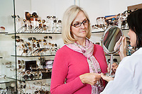 Optician holding mirror while senior female customer looking