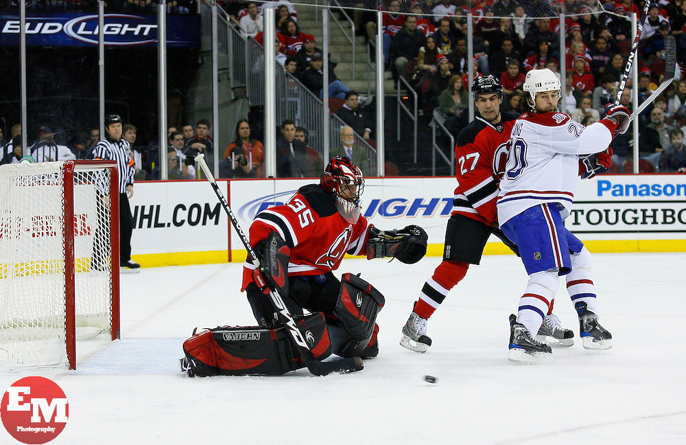 Jan 2, 2009; Newark, NJ, USA; New Jersey Devils defenseman Mike Mottau (27) and Montreal Canadiens center Robert Lang (20) battle while New Jersey Devils goalie Scott Clemmensen (35) makes a save during the first period at the Prudential Center.