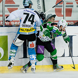 Matej Hocevar (HDD Tilia Olimpija, #14) and Daniel Oberkofler (EHC Liwest Linz, #74) during of ice-hockey match between HDD Tilia Olimpija and EHC Liwest Linz in 15th Round of EBEL league, on October 25, 2011 at Hala Tivoli, Ljubljana, Slovenia. (Photo By Matic Klansek Velej / Sportida)