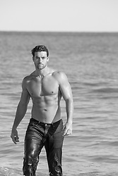 shirtless muscular man coming out of the ocean in wet jeans