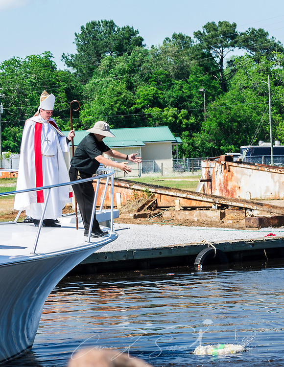The Rev. Bieu Nguyen, pastor of St. Margaret's Catholic Church, tosses a ceremonial wreath in the bayou as Catholic Archbishop Thomas J. Rodi watches during the 65th annual Blessing of the Fleet in Bayou La Batre, Alabama, May 4, 2014. The first fleet blessing was held by St. Margaret's Catholic Church in 1949, carrying on a long European tradition of asking God's favor for a bountiful seafood harvest and protection from the perils of the sea. The highlight of the event is a blessing of the boats by the local Catholic archbishop and the tossing of a ceremonial wreath in memory of those who have lost their lives at sea. The event also includes a land parade and a parade of decorated boats that slowly cruise through the bayou. (Photo by Carmen K. Sisson/Cloudybright)