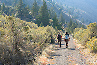 Two women hiking on dirt road trail Deschutes River canyon of Oregon USA.