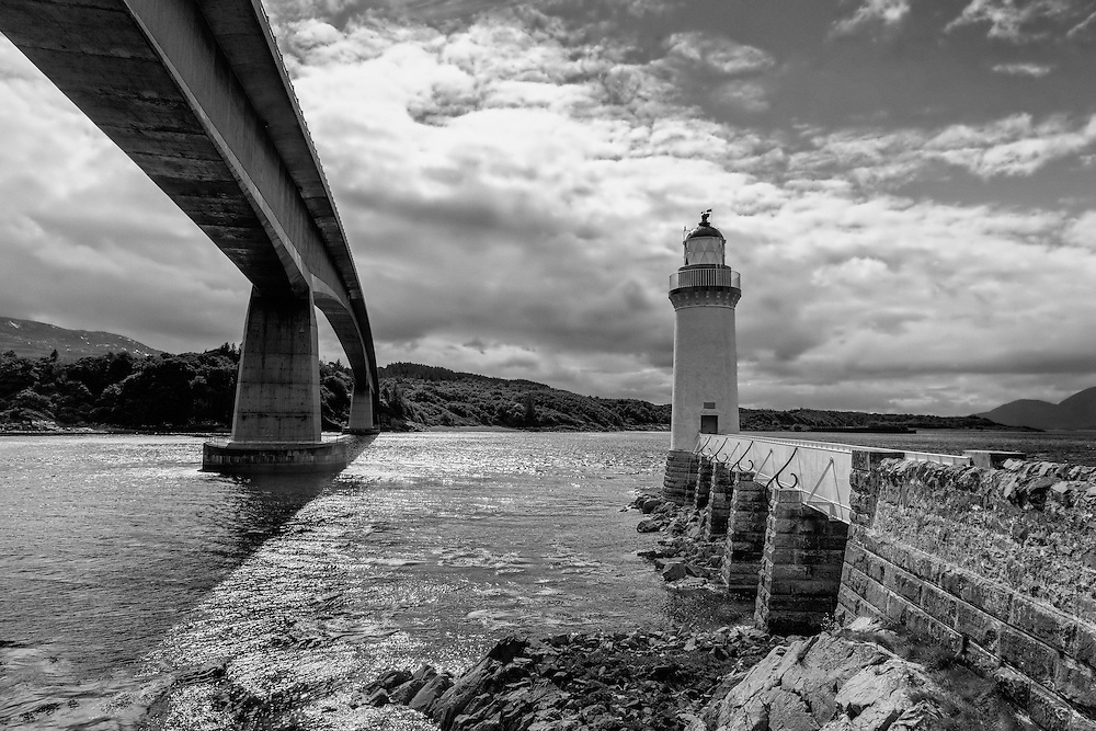 The Eilean Bån Lighthouse is situated between Kyleakin on the Isle of Skye and Kyle of Lochalsh on mainland Scotland. <br /> <br /> Eilean Bàn means White Island is a six-acre nature haven nestling below the Skye road bridge that spans between the maninland and the Isle.<br /> <br /> The island was originally home just to the lighthouse keepers and their families, it later became the residence of the author and naturalist, Gavin Maxwell.<br /> <br /> The 70 foot tall lighthouse was designed by David (1815-81) and Thomas (1818-87) Stevenson, and built in 1857. Thomas Stevenson was the father of the author Robert Louis Stevenson (1850-94).<br /> <br /> When first built the light itself was fuelled by sperm whale oil, and displayed a central white beam flanked by a red and a green beam.<br /> <br /> It was not until 1898 that the lamp was converted to a paraffin vapour system<br /> <br /> The lighthouse was finally decommissioned in 1993. The channel into Loch Alsh was then marked by the large red and green buoys that can be seen running east and west from the lighthouse. After decommissioning the lighthouse was denoted as a day mark, which means that it remains a landmark that it is used for navigation during the day, and must therefore continue to be kept in good condition.<br /> <br /> This photograph is a monochromatic view of Eilean Ban Lighthouse, looking across to the Isle of Skye. The photograph can be purchased as print, mounted print in frames, canvas or aluminum or as a digital file.