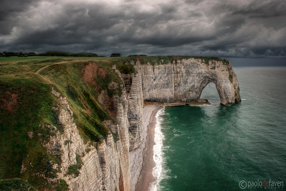 "A moody representation, with an incoming storm in the background, of the cliff known as La Manneporte, which is part of the amazing rocky coast around Etretat in Upper Normandy, France, altogether known as Les Failases d'Etretat..La Manneporte, which in French means ""the great door"" is one of the most beloved subject of the famous French impressionist painter Claude Monet, who depicted it in more of 40 paints..Monet loved very much Etretat and its cliffs, and settled here his house and atelier for years.."