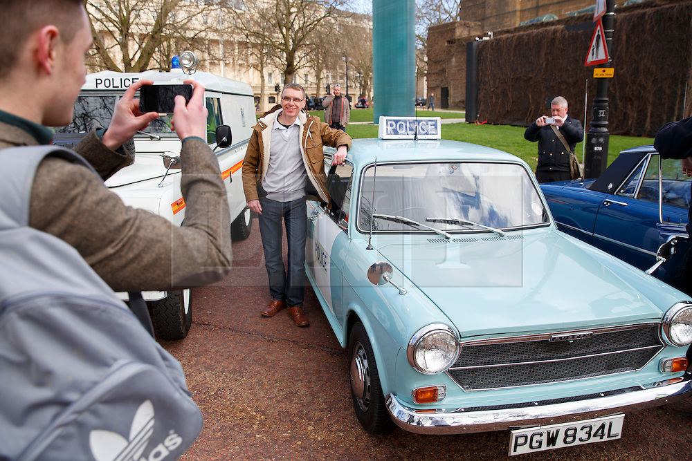 © licensed to London News Pictures. London, UK 26/02/2014. People posing with veteran police cars outside as the Met's iconic cop cars dating back to 1948 taking part at a convoy through central London. Vehicles including the 1948 Wolseley, 1970 Morris, Minor 1000 and the 1973 Special Branch Rover P6 leaving Hampton Traffic Garage for the final time to head up to the Met's Peel Centre in Hendon which will be the new home of the fleet. Photo credit: Tolga Akmen/LNP