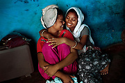 After having washed her hair, Poonam, 13, (left) is being hugged by her oldest sister Arti, 19, while sitting on the floor of their newly built home in Oriya Basti, one of the water-contaminated colonies in Bhopal, central India, near the abandoned Union Carbide (now DOW Chemical) industrial complex, site of the infamous '1984 Gas Disaster'.