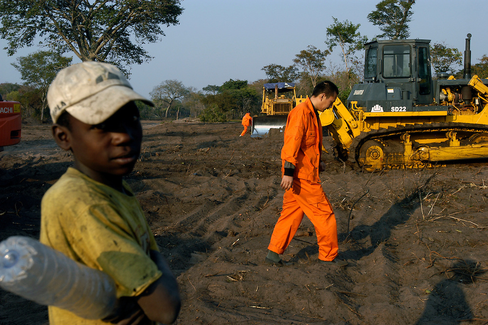 Chinese contractors and Angolan workers building a road in the eastern province of Moxico. After decades of war, the country is undergoing a vast reconstruction program..Cazaji, Angola. 28/07/2008..Photo © J.B. Russell
