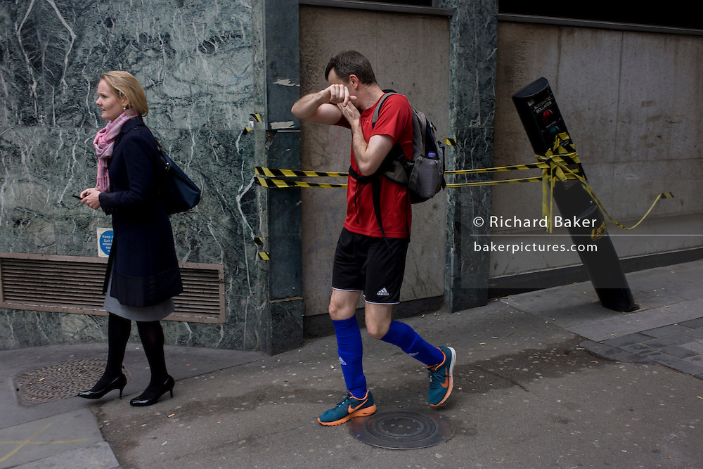 A jogger wipes his brow as he passes a leaning automatic traffic control bollard in St . Swithins Lane, City of London.