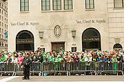 Spectators,many wearing green, line Fifth Avenue in front of the jeweller Van Cleef & Arpels.