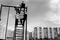 Children playing on climbing frame near block of flats<br />