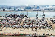 Nederland, Zuid-Holland, Rotterdam, 10-06-2015; Ultra Large Container Carrier Cosco England voor de kade van de Euromax terminal, Yangtzehaven. In de achtergrond de E.ON centrale op de Maasvlakte.<br /> Container Ship at the quay of the Euromax terminal, Yangtzehaven.<br /> luchtfoto (toeslag op standard tarieven);<br /> aerial photo (additional fee required);<br /> copyright foto/photo Siebe Swart