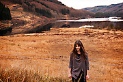 Southern Uplan Way, Glen Trool, Young woman with long brown hair stands against a backdrop of hills and water on an overcast day.