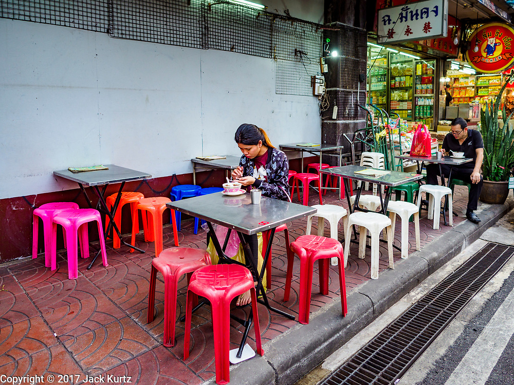 """18 MAY 2017 - BANGKOK, THAILAND: People eating at a street food stall in Bangkok's Chinatown. City officials in Bangkok have taken steps to rein in street food vendors. The steps were originally reported as a """"ban"""" on street food, but after an uproar in local and international news outlets, city officials said street food vendors wouldn't be banned but would be regulated, undergo health inspections and be restricted to certain hours on major streets. On Yaowarat Road, in the heart of Bangkok's touristy Chinatown, the city has closed some traffic lanes to facilitate the vendors. But in other parts of the city, the vendors have been moved off of major streets and sidewalks.      PHOTO BY JACK KURTZ"""