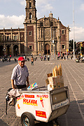 An ice cream seller pushes his cart past the Church of Santo Domingo in Santo Domingo plaza in the historic center of Mexico City, Mexico.