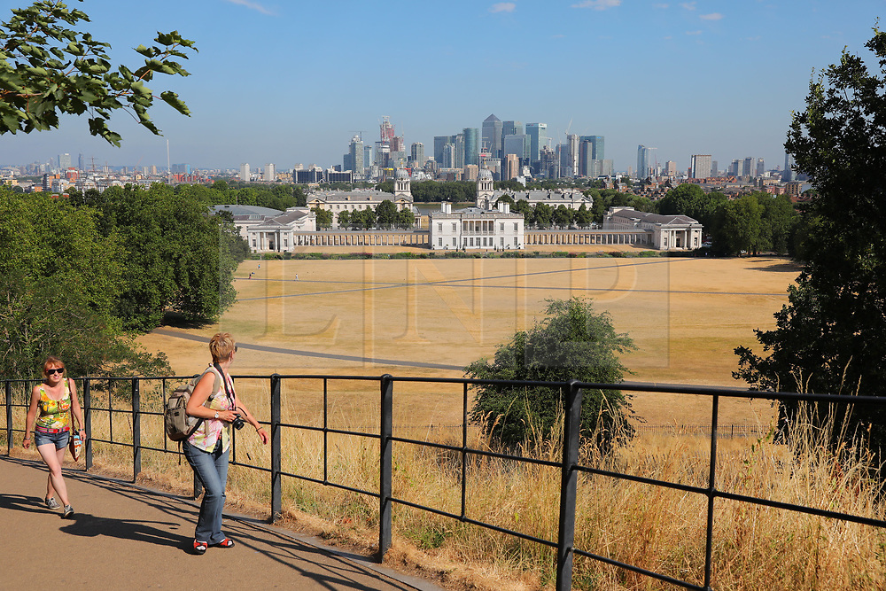 © Licensed to London News Pictures. 24/07/2018. London, UK. People looking out over Canary Wharf from Greenwich Park at the start of another hot day in London. Record temperatures are expected to continue throughout the week. Photo credit: Rob Pinney/LNP