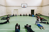 """NAPLES, ITALY - 16 MARCH 2018: Teenagers do yoga during a warm-up session before a parkour class at """"Il Tappeto di Iqbal"""" (Iqbal's carpet), a non-profit cooperative in Barra, the estern district of Naples, Italy, on March 16th 2018.<br /> <br /> Il Tappeto di Iqbal (Iqbal's Carpet) is a non-profit cooperative founded in 2015 and Save The Children partner since 2015 that operates in the Naple's eastern neighborhood of Barra children in the arts of circus, theater and parkour. It was named after Iqbal Masih, a Pakistani boy who escaped from life as a child slave and became an activist against bonded labor in the 1990s.<br /> Barra, which is home to some 45,000 people, has the highest rate of school dropouts in the Italian region of Campania. Once a thriving industrial community, many of the factories were destroyed in a 1980 earthquake and never rebuilt. The resulting de-industrialization turned Barra into a poor, decaying neighborhood. There are no cinemas, theaters, parks or public spaces in Barra.<br /> The vast majority of children from poor families are faced with the choice of working in the black economy or joining the ranks of the organised crime.<br /> Recently, Save the Children Italy opened a number of educational and social spaces in Barra. The centers, known as Punti Luce, or points of light, aim to help local kids stay out of the ranks of the organised crime and have also become hubs for Iqbal's Carpet to work."""