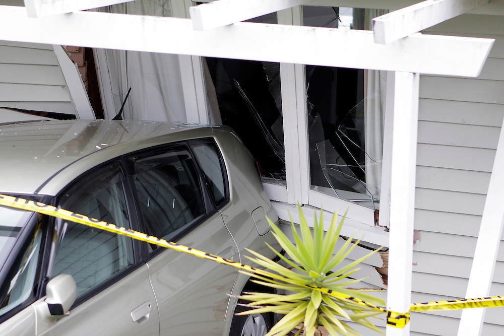 A vehicle rests in a house after rolling down a driveway on the opposite side of the road and crashing through a fence and deck, Auckland, New Zealand, Tuesday, May 08, 2012. Credit:SNPA / Bradley Ambrose
