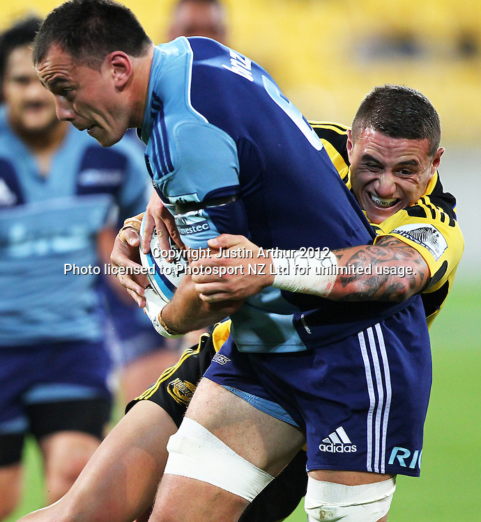 Hurricanes' TJ Perenara makes a tackle on Blues' Chris Lowrey during the 2012 Super Rugby season, Hurricanes v Blues at Westpac Stadium, Wellington, New Zealand on Friday 4 May 2012. Photo: Justin Arthur / photosport.co.nz