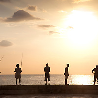 Fishing along the Malecon in Havana, Cuba, at sunset