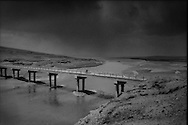 """Tibetan men cross one the first bridges to span the Yellow River running low in late-spring/early summer near its source, as it moves between the twin great lakes, Ngoring and Gyaring, in the Sanjiangyuan Reserve.  It should be at its highest water level at this time of year.  This is one of the coldest places of the Tibet Plateau at an elevation of between 4,300m - 4,700m (14,100 ft - 15,400 ft), where wintertime temperatures can fall to -30C (-22F) or colder in this treeless landscape. This is the territory of the Golok nomads, renown throughout Tibet for their ferocity as warriors and bandits.  As a part of establishing the Sanjiangyuan Reserve, which encompasses the headwaters of the Yellow, Yangtze and Mekong Rivers, most of the nomadic families have been forced to settle in towns like Madoi.  """"Madoi"""" means source of the Yellow River in Tibetan."""