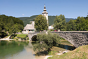 Church in village, bridge over Bohinj Lake. Slovenia. Eastern Europe.