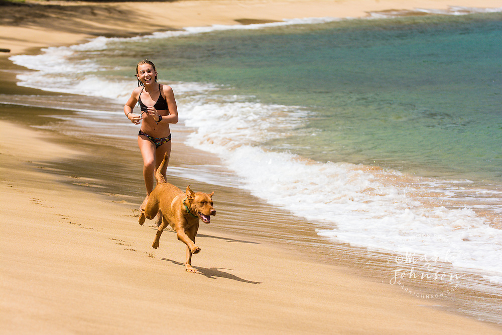 10 year old girl playing at the beach with her dog, Hanalei, Kauai, Hawaii