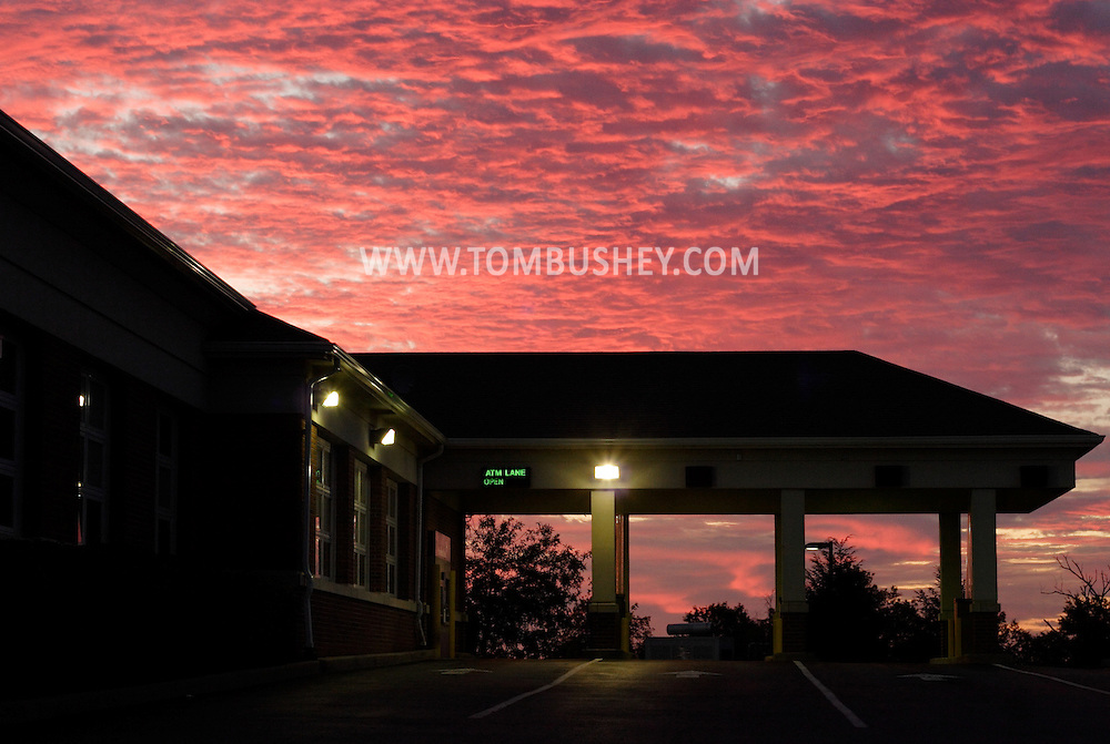 Town of Wallkill, N.Y. - The rising sun turns clouds pink and purple behind the empty  drive-thru lanes at Provident Bank on Aug. 21, 2006.