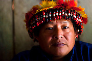 """Simon Weepiu, """"Apu"""" or leader of a aguaruna community posses for a portrait at his house near to Imaza river-port of the Mara-on river in Amazons district, Peru. After the events of June 5 in the Amazonian province of Bagua, in northeastern Peru, where 24 policemen and a number still not confirmed of natives from the communities of the ÒAlto Mara-onÓ and civilians died in clashes after a series of demonstrations in opposition to the approval by the Peruvian government, for a group of ordinances that allow large flexibility in the restrictions on resource extraction in the area, breaking the 169 agreement of ILO (International Labour Organization), which requires the consultation of indigenous communities about the exploitation of nature in their territories. One of the most active communities was the awajun, a warlike and revengeful people, heritors of the Jibaros and recently contacted near to 1950. For the leader or """"apu"""" for one of the aguarunas riverside communities of the Mara-on, Simon Weepiu, Òthe force of this movement come from the conviction of the struggle, which is caused by the ancestral development as based on worldview, which provides the native of a special power, that of becoming one with his idea and his brothers, to focus all on the same objective and be just a great strength."""" The government aims to generate development in the area allowing the exploitation of property, The jungle is rich in gold and oil, and even argue that natural wealth of the region belong to all Peruvians, and not just the communities that inhabit it, but acts as the oil«s filtration to waters of the Mara-on, left in evidence that in a complex ecosystem like jungle that mixed spilled oil by rain in the river, home to fishes, as well as the waters that irrigate cassava, bananas, sugarcane and other elements vital to the development of communities. The natives, insist that the forest is not only home, is where they get medicines to cure their sick and food for their families."""