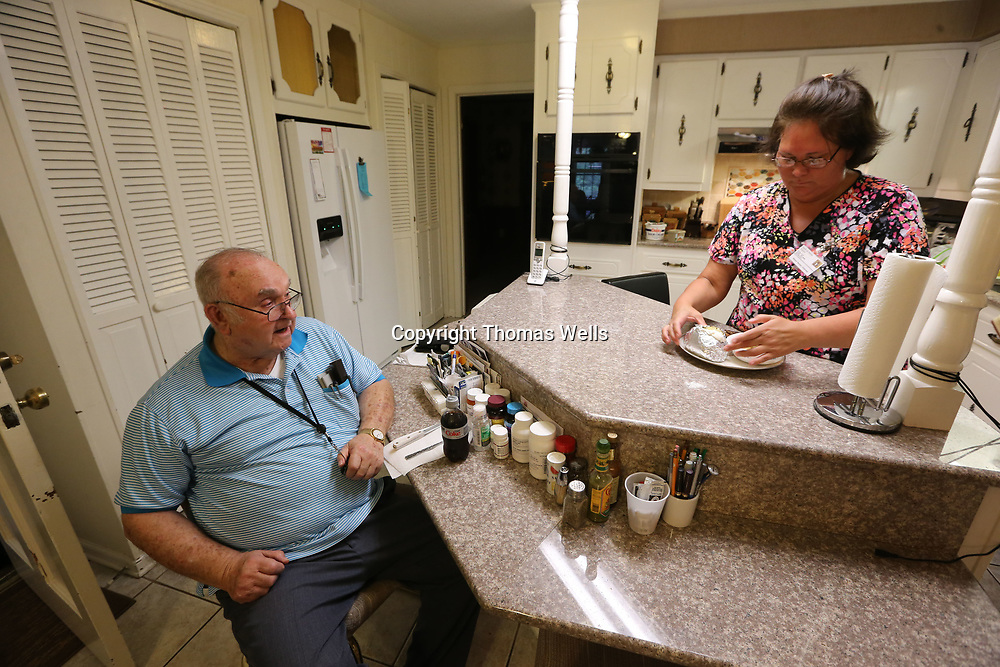 Edward Ford, left, sits close by as he watches his caregiver Denise Chatmen prepare his supper at his home in Tupelo.