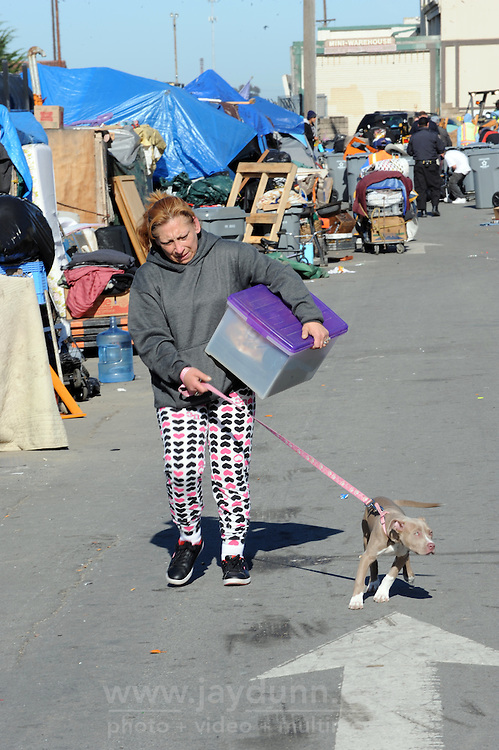 A resident moves what she can under police supervision during a sweep of homeless encampments in Salinas on Thursday, March 24th in the Market Way area of Chinatown.