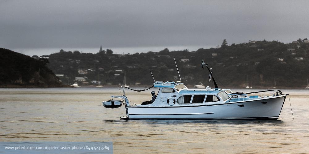The launch Jolly Roger, anchored and fishing, early morning, in rain, off Matarahui Bay and Huruhi Bay, Waiheke Island, Hauraki Gulf, Auckland, New Zealand.