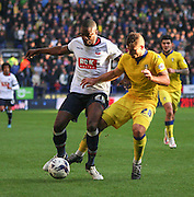 Shola Ameobi and Lewis Cook battle during the Sky Bet Championship match between Bolton Wanderers and Leeds United at the Macron Stadium, Bolton, England on 24 October 2015. Photo by Pete Burns.