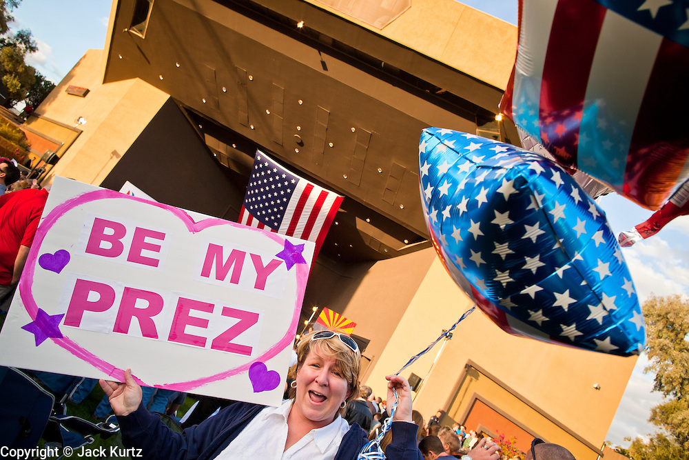 13 FEBRUARY 2012 - MESA, AZ: STEFANY CLARK from Litchfield Park, AZ, carries signs for Mitt Romney in Mesa. Clark said she has been a long time member of the Tea Party but that she's supported for a longer time. Several thousand people crowded into the Mesa Amphitheatre in Mesa, AZ, Monday night to hear Republican Presidential candidate Mitt Romney speak. Romney, a Mormon, is expected to win in Arizona, which has a large Mormon population. Arizona's Republican Presidential primary is February 28.        PHOTO BY JACK KURTZ
