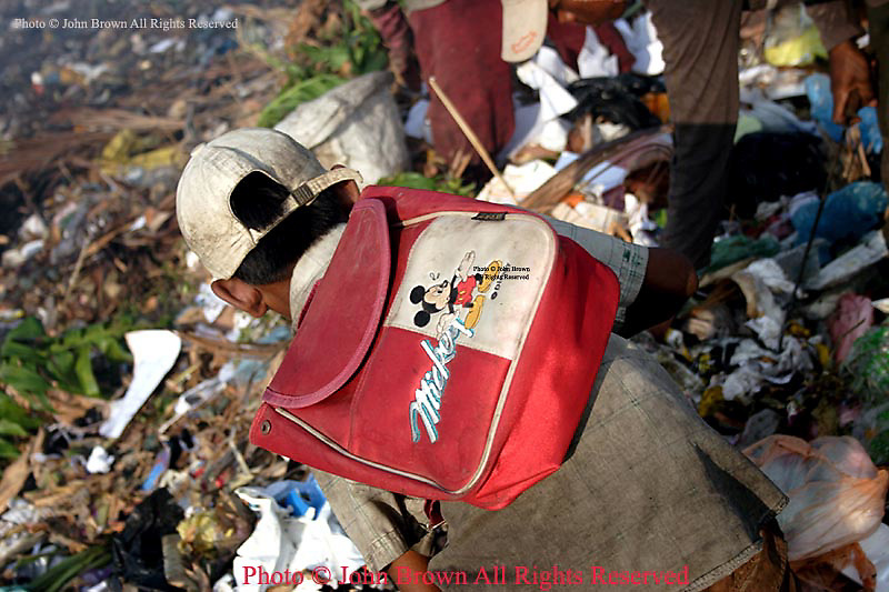 A young worker wears a Mickey Mouse backpack while performing his duties as a scavenger at The Stung Meanchey Landfill in Phnom Penh, Cambodia. He is one of 600 children who work at the dump on a daily basis. Most all of the children are too poor to attend school.