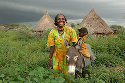 Aifa Aifa stands together with her new donkey that she chose at the bustling Thursday livestock market in Barentu, Eritrea August 30, 2006.