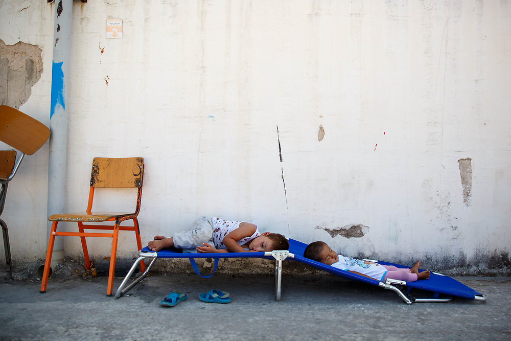 Afghan children take a nap in the stifling heat. They are among the 60,000 refugees stranded in Greece after the Balkan borders closed to all refugees in March 2016. Oinofyta Refugee Camp for Afghans, Greece, July 2016.