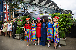 © Licensed to London News Pictures. 19/06/2018. London, UK.  A group of colourfully dressed racegoers pose for a photograph while attending day one of Royal Ascot at Ascot racecourse in Berkshire, on June 19, 2018. The 5 day showcase event, which is one of the highlights of the racing calendar, has been held at the famous Berkshire course since 1711 and tradition is a hallmark of the meeting. Top hats and tails remain compulsory in parts of the course. Photo credit: Ben Cawthra/LNP