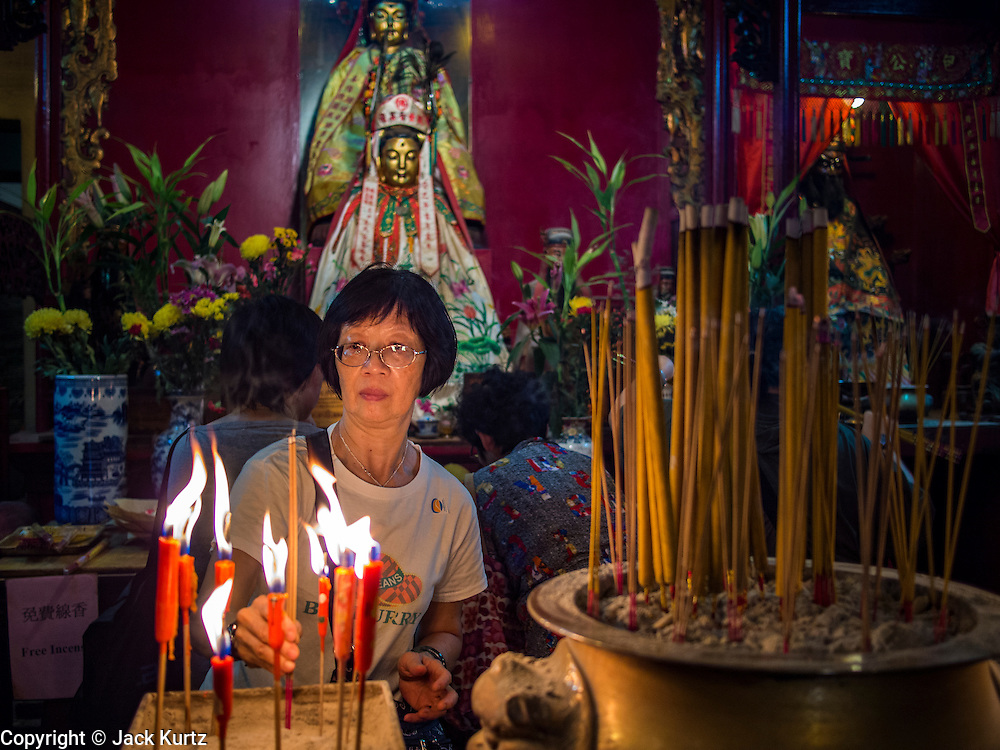 10 AUGUST 2013 - HONG KONG:  A woman prays in Man Mo Temple in Hong Kong. Hong Kong is one of the two Special Administrative Regions of the People's Republic of China, Macau is the other. It is situated on China's south coast and, enclosed by the Pearl River Delta and South China Sea, it is known for its skyline and deep natural harbour. Hong Kong is one of the most densely populated areas in the world, the  population is 93.6% ethnic Chinese and 6.4% from other groups. The Han Chinese majority originate mainly from the cities of Guangzhou and Taishan in the neighbouring Guangdong province.      PHOTO BY JACK KURTZ