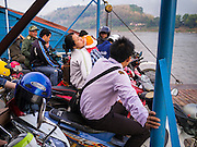 11 MARCH 2013 - ALONG HIGHWAY 13, LAOS: A woman balances her child on her motorcycle while she rides a ferry across the Mekong River near Luang Prabang. The Mekong River ferries are disappearing as bridges across the river are completed and roads along the river are paved. The paving of Highway 13 from Vientiane to near the Chinese border has changed the way of life in rural Laos. Villagers near Luang Prabang used to have to take unreliable boats that took three hours round trip to get from the homes to the tourist center of Luang Prabang, now they take a 40 minute round trip bus ride. North of Luang Prabang, paving the highway has been an opportunity for China to use Laos as a transshipping point. Chinese merchandise now goes through Laos to Thailand where it's put on Thai trains and taken to the deep water port east of Bangkok. The Chinese have also expanded their economic empire into Laos. Chinese hotels and businesses are common in northern Laos and in some cities, like Oudomxay, are now up to 40% percent. As the roads are paved, more people move away from their traditional homes in the mountains of Laos and crowd the side of the road living off tourists' and truck drivers.    PHOTO BY JACK KURTZ